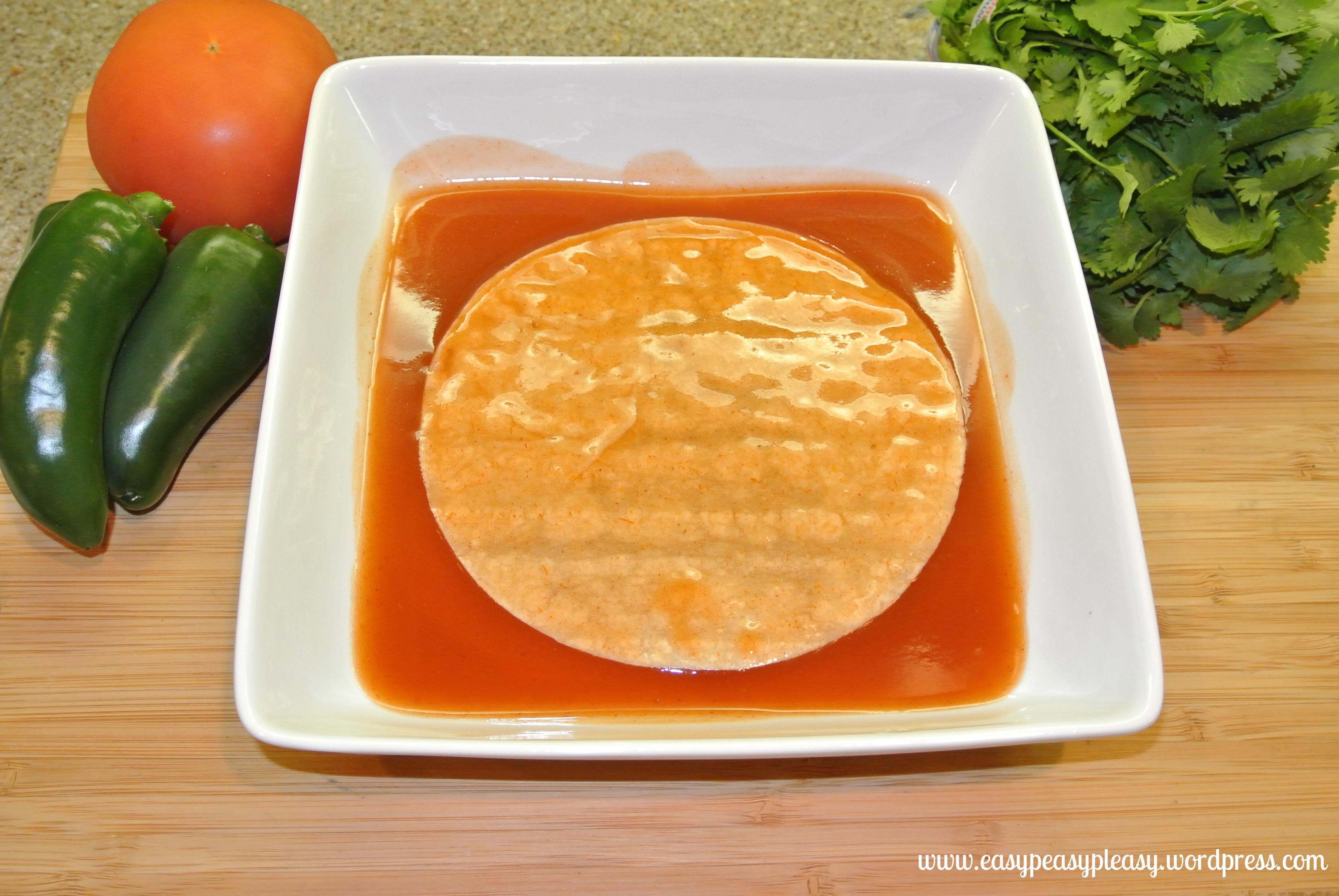 Turkey Enchilada Casserole adding flavor by running the corn tortilla through the enchilada sauce